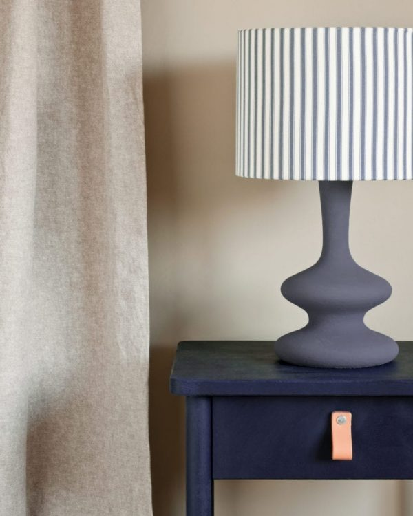Oxford-Navy-side-table-curtain-in-Linen-Union-in-Old-White-French-Linen-lamp-base-in-Old-Violet-lampshade-in-Ticking-in-Old-Violet